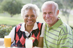 Couple Enjoying A Beverage By A Golf Course Royalty Free Stock Image