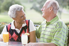 Couple Enjoying A Beverage By A Golf Course Royalty Free Stock Photos
