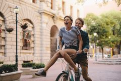 Couple enjoying a bicycle ride in the city. Couple enjoying on a bicycle in the city. Cheerful women sitting on handlebar of boyfriends bicycle royalty free stock images