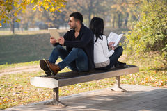 Couple Enjoying Book And Digtial Tablet Touchpad Stock Photos