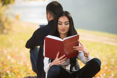 Couple Enjoying Book And Digtial Tablet Touchpad Royalty Free Stock Photos