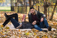 Couple Enjoying Book Reading In Autumn Park Royalty Free Stock Photography