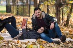 Couple Enjoying Book Reading In Autumn Park Stock Photo