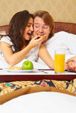 Couple enjoying breakfast on bed Stock Photo