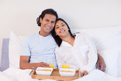 Couple enjoying breakfast in the bed Stock Images