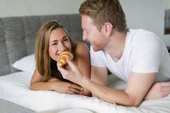 Couple enjoying breakfast in bed. Happy couple in love enjoying breakfast in bed Stock Photos