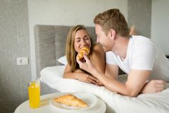 Couple enjoying breakfast in bed. Happy couple in love enjoying breakfast in bed Royalty Free Stock Photos