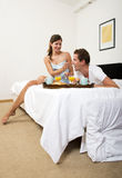 Couple enjoying a breakfast in bed together royalty free stock photography