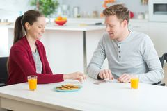 Couple enjoying breakfast together at home. Couple enjoying a breakfast together at home Stock Images