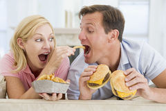 Couple Enjoying Burgers Together Royalty Free Stock Photos