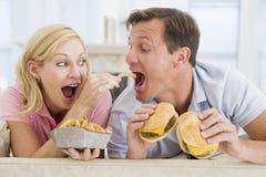Couple Enjoying Burgers Together Royalty Free Stock Photos