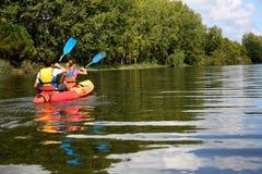 Couple enjoying canoe ride on sunny day. Couple riding canoe in river Stock Photo