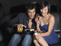 Couple Enjoying Champagne In Limousine Stock Photos