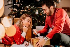 couple enjoying Christmas morning and opening gifts wearing matching sweaters stock photos