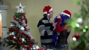 Couple enjoying Christmas time while decorating tree stock footage