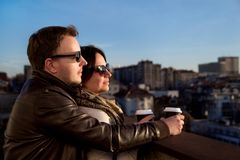 Couple enjoying city skyline while drinking coffee on sunny day royalty free stock photo