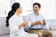 Couple enjoying coffee on the couch Stock Photography