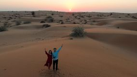 Couple enjoying desert sunset aerial view stock video footage
