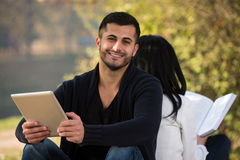 Couple Enjoying Digtial Tablet And Book Royalty Free Stock Photos