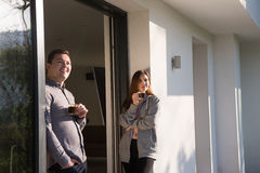 Couple enjoying on the door of their luxury home villa. Young beautiful handsome couple enjoying morning coffee on the door of their luxury home villa royalty free stock photography