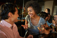 Couple Enjoying Drink At Bar With Friends Stock Image