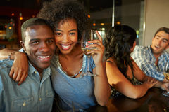 Couple Enjoying Drink At Bar With Friends. Smiling To Camera Royalty Free Stock Photography