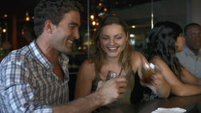 Couple Enjoying Drink At Bar Together. Young couple enjoying a night out in bar.Shot on Sony FS700 in PAL format at a frame rate of 25fps stock video footage