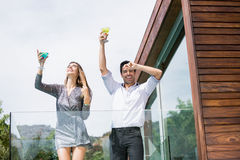 Couple enjoying drinks in balcony Stock Images