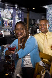 Couple enjoying drinks at bar Stock Photos