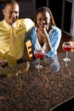 Couple enjoying drinks at a bar Stock Images