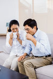 Couple enjoying drinks on the couch Stock Images