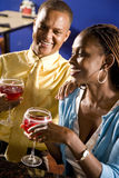 Couple enjoying drinks in restaurant Stock Image