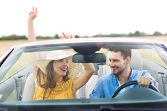 Couple enjoying a drive in a convertible Royalty Free Stock Photos