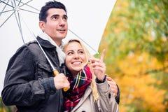 Couple enjoying fall day having walk despite the rain Royalty Free Stock Photos