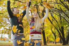 Couple enjoying falling autumn leaves in park stock image
