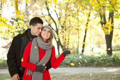 Couple enjoying the falling leaves Royalty Free Stock Photo