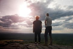 Couple enjoying fantastic moments during sunset . Young pair of hikers on the peak of rock empires park and watch over valley. Royalty Free Stock Photography
