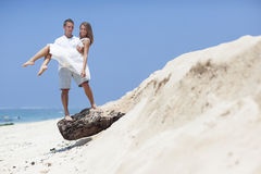 COUPLE ENJOYING FREEDOM ON THE BEACH Royalty Free Stock Images