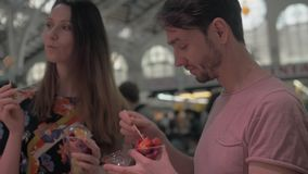 Couple enjoying fruit snack in the cups. Young couple having a snack with fresh fruit salad in plastic cups at the shopping gallery. Man treating girlfriend with stock video
