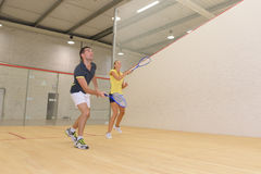 Couple enjoying game squash in squash court Royalty Free Stock Images