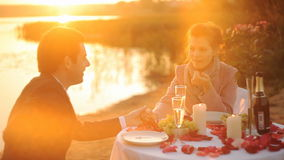 Couple enjoying glass of champagne on beach at sunset stock video footage