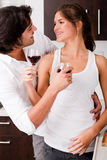Couple enjoying a glass of wine. Happy young couple enjoying their wine in kitchen stock photos
