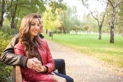 Couple enjoying golden autumn fall season in park Stock Photography