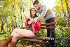 Couple enjoying golden autumn fall season in park Stock Images