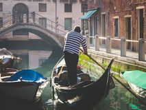 Couple enjoying gondola tour in the water channel of Venice. Vintage photo Stock Images