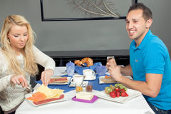Couple enjoying a hearty breakfast. Happy friendly young couple seated at a restaurant table enjoying a hearty breakfast with a spread of fresh fruit, rolls Stock Photo