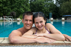 Couple enjoying holidays at pool edge Royalty Free Stock Photos