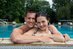 Couple enjoying holidays at pool edge Stock Photo