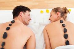 Couple enjoying a hot stone massage Royalty Free Stock Photography