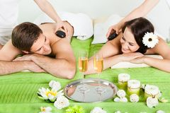 Couple enjoying hot stone massage at spa Stock Photos